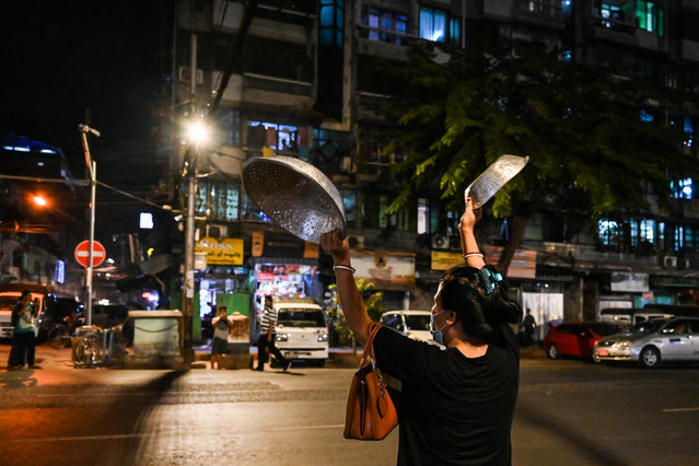 A woman clatters pans to make noise after calls for protest went out on social media in Yangon on February 3, 2021, as Myanmar's ousted leader Aung San Suu Kyi was formally charged on Wednesday two days after she was detained in a military coup. (Photo by AFP Photo/Stringer)