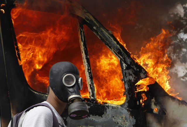 A protester wearing a gas mask walks beside a burning van during violent protests against austerity measures in Athens, in this June 28, 2011 file photo. (Photo by Yannis Behrakis/Reuters)