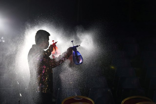 A staff member from 'Circo Pastelito' sprays disinfectant ahead of opening the circus under a sanitary protocol against COVID-19 spread in Santiago, Chile, November 25, 2020. (Photo by Ivan Alvarado/Reuters)