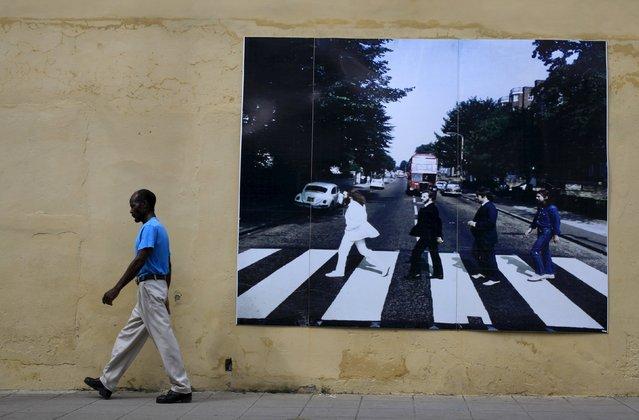 A man walks near a picture of The Beatles in Camaguey province, Cuba November 12, 2015. Picture taken November 12, 2015. (Photo by Enrique de la Osa/Reuters)