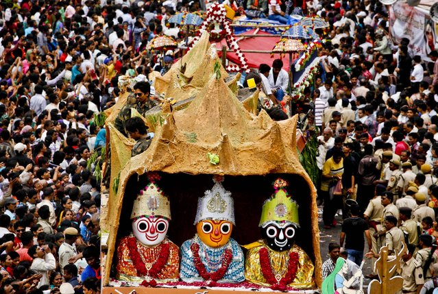 Thousands of devotees participate in the annual chariot procession of Hindu god Lord Jagannath in Ahmadabad, India, on July 10, 2013. During the festival of the Hindu god, his brother Balabhadra and sister Subhadra are taken out in a grand procession in specially made chariots pulled by thousands of devotees. (Photo by Ajit Solanki/Associated Press)