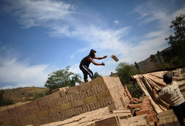 A worker standing on a pile of bricks receives bricks from another worker at a brick factory in Tixtla, on the outskirts of Chilpancingo, in the Guerrero state, January 26, 2015. (Photo by Jorge Dan Lopez/Reuters)