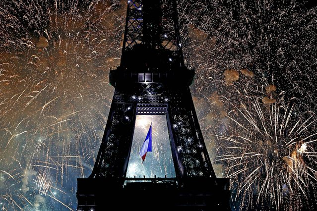 The Eiffel Tower is illuminated during the traditional Bastille Day fireworks display, on July 14, 2013. (Photo by Charles Platiau/Reuters)