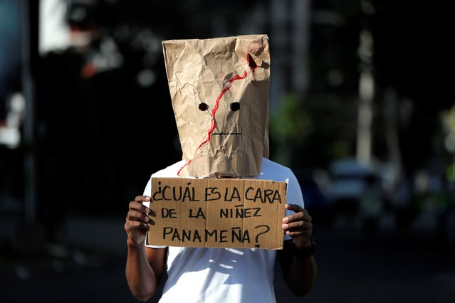 """A person with the face covered shows a protest poster that reads: """"What is the face of Panamanian children?"""", during a new demonstration against child sexual abuse, in front of the headquarters of the National Secretariat for Children, Adolescents and the Family (Senniaf), in Panama City, Panama, 26 February 2021. Two weeks ago, a parliamentary subcommittee uncovered a scandal of sexual abuse and physical and psychological mistreatment of dozens of minors since 2015 in shelters under state supervision. The events have provoked a wave of social indignation for weeks with demonstrations throughout the country to demand justice. The scandal has led to Panama's attorney general Eduardo Ulloa's to announce his """"irrevocable resignation"""" last Wednesday. (Photo by Bienvenido Velasco/EPA/EFE)"""