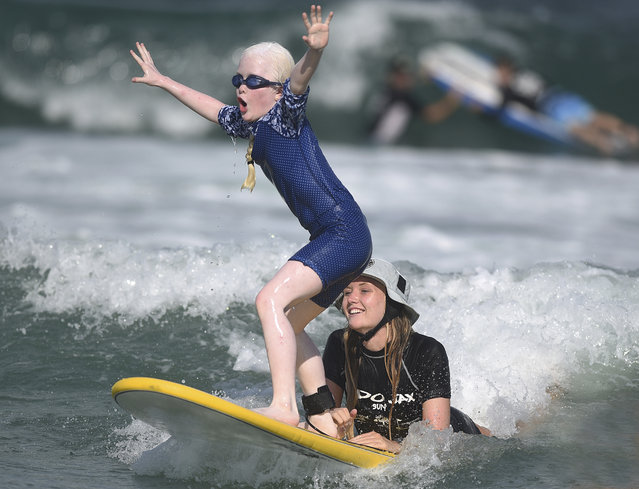 Carly Long, 10, of Charlotte, N.C., catches a wave as instructor Molly Gilbert rides on the back of the board during Indo Jax Surf School's 11th annual visually impaired surf camp at Wrightsville Beach, N.C., Thursday, July 19, 2018. (Photo by Matt Born/The Star-News via AP Photo)