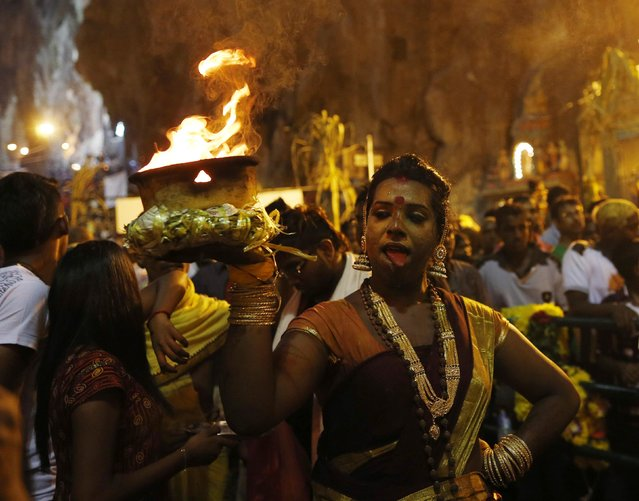 A Hindu devotee carries a flaming pot while on her pilgrimage to the Batu Caves temple during Thaipusam in Kuala Lumpur February 3, 2015. (Photo by Olivia Harris/Reuters)