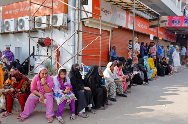 Women sit in a queue to deposit or exchange their old high denomination banknotes outside a bank in Ahmedabad, India, November 16, 2016. (Photo by Amit Dave/Reuters)
