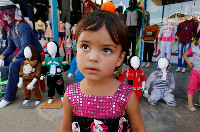 Syrian refugee, Samah Aloshi, 3, stands in front of a clothing shop Zaatari refugee camp near the border with Syria, in Mafraq, Jordan October 16, 2016. (Photo by Ammar Awad/Reuters)