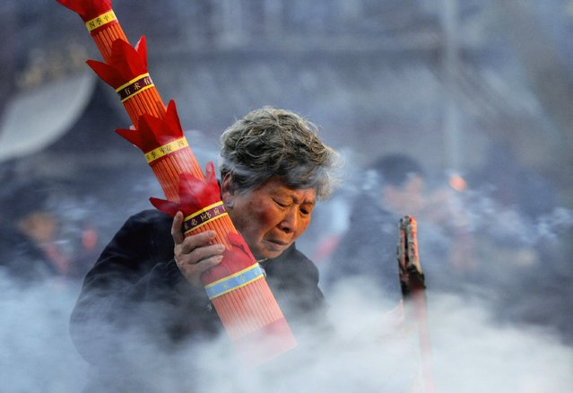 A woman burns incense during Laba Festival at a Buddhist temple in Huaian, Jiangsu province, January 27, 2015. (Photo by Reuters/Stringer)
