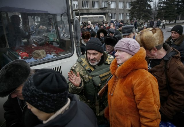 A member of the Ukrainian armed forces assists local residents onto a bus to flee the military conflict, in Debaltseve, eastern Ukraine, February 6, 201. (Photo by Gleb Garanich/Reuters)