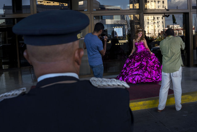 In this December 13, 2015 photo, Amanda Teresa Betancourt, who lives in Cuba, poses during a quinceanera photo session as a hotel doorman stands by in Havana, Cuba. Cuban reforms permitting small-scale, private businesses and the re-establishment of U.S.-Cuban diplomatic relations have encouraged new photo and event planning businesses for events such as girls' 15th birthdays. (Photo by Ramon Espinosa/AP Photo)
