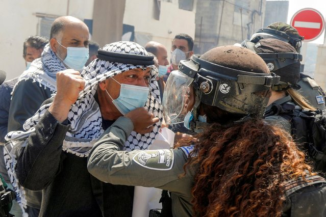 """A Palestinian demonstrator scuffles with an Israeli border policewoman during a protest marking """"Land Day"""", in Sebastia near Nablus, in the Israeli-occupied West Bank on March 30, 2021. (Photo by Raneen Sawafta/Reuters)"""