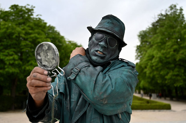 Cuban street performer Ricardo Elias Hardy, 57, dresses himself up to perform as a living statue at the Retiro park in Madrid on April 1, 2021. As a living-statue, Elias Hardy stands motionless, sporting realistic statue-like makeup to get tips from tourists and passers-by. (Photo by Gabriel Bouys/AFP Photo)