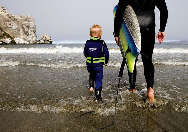 Triston and his father hit the waves. (Photo by Joe Johnston/The Tribune of San Luis Obispo)