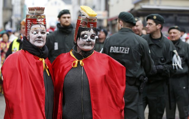 Carnival revellers stand in front of police during the traditional Rose Monday carnival parade in Cologne February 16, 2015. (Photo by Wolfgang Rattay/Reuters)