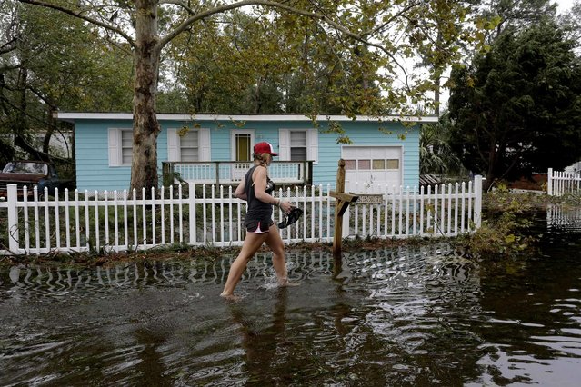 Jayme Cayton walks up to her flooded home for the first time after Hurricane Florence hit Emerald Isle N.C.,Sunday, September 16, 2018. (Photo by Tom Copeland/AP Photo)