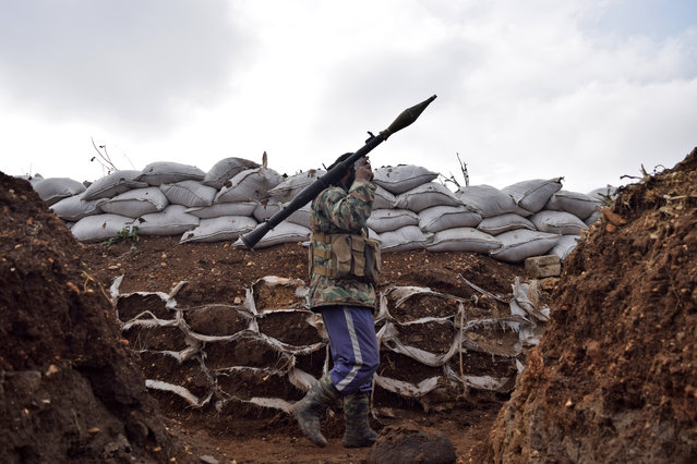 An opposition fighter from the Sham brigade walks holding a rocket-propelled grenade in a trench on the front line during the ongoing clashes with government forces in the village of Teir Maalah in Syria's central Homs province on December 5, 2016. (Photo by Mahmoud Taha/AFP Photo)