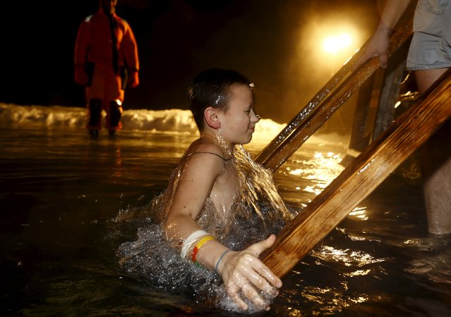 A boy dips into the icy waters of a lake as part of celebrations for Orthodox Epiphany on the outskirts of Minsk, January 18, 2016. (Photo by Vasily Fedosenko/Reuters)
