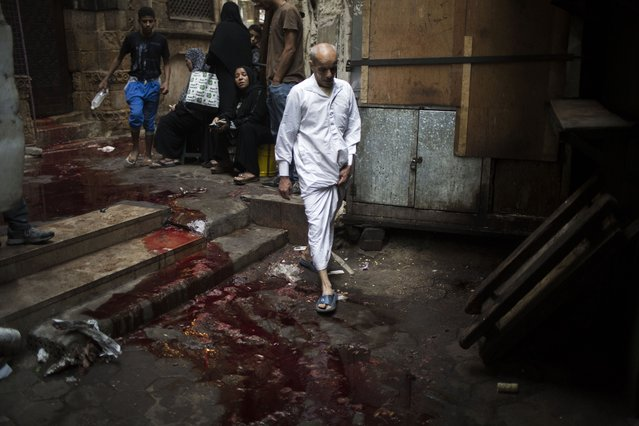 A man walks through an alley covered with bloodstained water on the first day of Eid al-Adha in Cairo, Egypt, Tuesday, October 15, 2013. Muslims worldwide are celebrating Eid al-Adha, or the Feast of the Sacrifice, by sacrificial killing of sheep, goats, cows or camels. The slaughter commemorates the biblical story of Abraham, who was on the verge of sacrificing his son to obey God's command, when God interceded by substituting a ram in the child's place. (Photo by Manu Brabo/AP Photo)