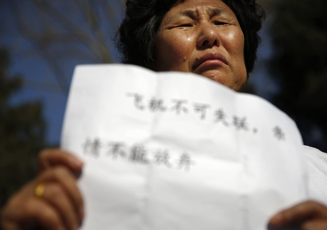"Liu Guiqiu, whose son was onboard the missing Malaysia Airlines flight MH370, cries as she holds a sign during a gathering of family members of the missing passengers outside the Malaysian embassy in Beijing March 8, 2015. Malaysian and Chinese officials say they are committed to the search for MH370 and in assisting families who are still waiting for concrete information on what happened to their loved ones a year ago.  The sign reads, ""A plane cannot lose contact; and families cannot give up their affection for their relatives."" 