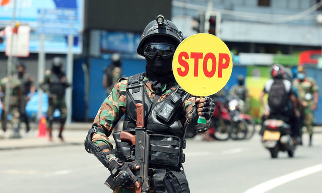 A member of special forces motorcycle teams stops vehicles for checking in Colombo, Sri Lanka, May 22, 2021. As over 50,000 people have been infected with the virus within the past one month alone, Sri Lankan authorities on Friday imposed an islandwide travel restriction, similar to a curfew, to prevent a further spread of the virus. (Photo by Xinhua News Agency/Rex Features/Shutterstock)