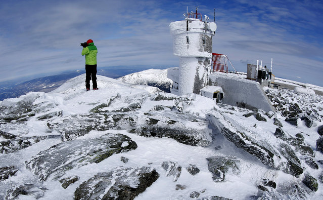 In this Tuesday, March 10, 2015 photo, Ryan Eyestone, 31, of Portland, Maine, makes a photographs near the weather instrument tower of the Mount Washington Observatory on the summit of Mount Washington in New Hampshire. (Photo by Robert F. Bukaty/AP Photo)