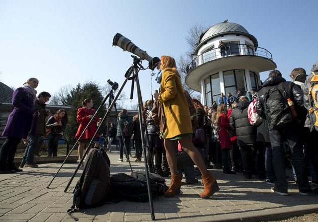 A woman looks at a partial solar eclipse through a camera's lens in central park in Minsk March 20, 2015. The moon covered about 70 percent of the sun in the capital of Belarus. (Photo by Vasily Fedosenko/Reuters)