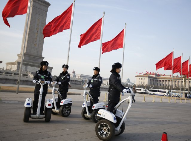 Police officers ride on motorized vehicles ahead of the third plenary meeting of the National People's Congress, China's parliament, outside the Great Hall of the People at the Tiananmen Square, in Beijing, March 12, 2015. (Photo by Iris Zhao/Reuters)