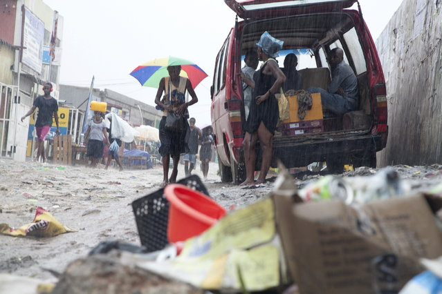 ANGOLA: People walk past a pile of garbage along a street during rainfall, in Luanda, Angola, February 10, 2016. (Photo by Herculano Corarado/Reuters)