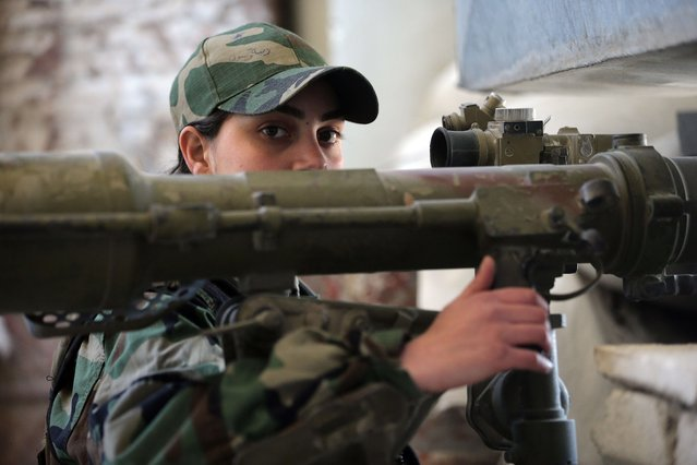 A female Syrian soldier from the Republican Guard commando battalion prepares to fire a B10 rocket during clashes with rebels in the restive Jobar area, in eastern Damascus, on March 25, 2015. (Photo by Joseph Eid/AFP Photo)