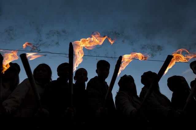 Young people hold torches as they ride an old, historical truck during a march from the Budapest University of Technology and Economics through the streets of Budapest, Hungary, to re-enact the protest march of Hungarian students in 1956 which ignited the revolution and war of independence against communist rule and the Soviet Union, 22 October 2018, the eve of the 62nd anniversary of the outbreak of the 1956 revolution in Hungary. (Photo by Marton Monus/EPA/EFE)