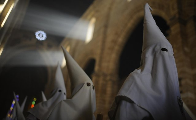 "Hooded penitents from ""La Borriquita"" brotherhood take part during a Holy Week procession in Cordoba, Spain, Sunday, March 29, 2015. (Photo by Manu Fernandez/AP Photo)"