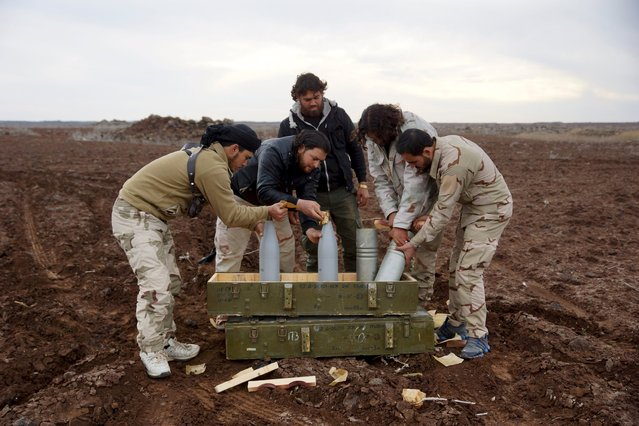 Mujahideen Horan brigade fighters, part of the Free Syrian Army, prepare shells before launching them towards forces loyal to Syria's President Bashar al-Assad located in Deraa, Syria, in what they said was a battle to pressure breaking the siege off Madaya, January 11, 2016. (Photo by Alaa Al-Faqir/Reuters)