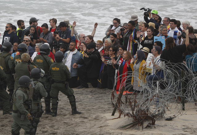 U.S. police and Border Patrol hold a line as members of an inter-faith group, showing support for Central American asylum-seekers who arrived in recent caravans and calling for an end to detaining and deporting immigrants, pray during a protest in San Diego, as seen from across the border wall in Tijuana, Mexico, Monday, December 10, 2018. The agents arrested dozens of protestors for trespassing as they tried to approach the border wall, and one person for assaulting an officer. (Photo by Rebecca Blackwell/AP Photo)