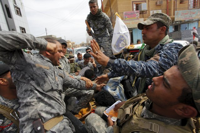 A member from the Iraqi security forces beats an Islamic State insurgent, who was captured in Tikrit April 1, 2015. Iraqi troops and Shi'ite paramilitary fighters were battling Islamic State on Wednesday in northern Tikrit, which officials described as the Sunni Muslim militant group's last stronghold in the city. (Photo by Alaa Al-Marjani/Reuters)