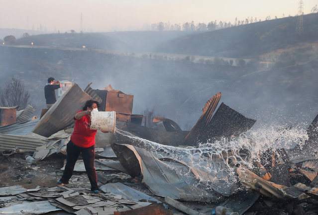 A woman throws water over her burned house on a hill, where more than 100 homes were burned due to a forest fire but there have been no reports of death, local authorities said in Valparaiso, Chile January 2, 2017. (Photo by Rodrigo Garrido/Reuters)