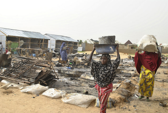 People walk through the debris at a camp for people displaced following an explosion by Islamist extremists, in Maiduguri, Nigeria, Thursday, June  8, 2017. Authorities in northeast Nigeria say at least six people are dead and dozens are wounded after Boko Haram militants launched a series of attacks during the Muslim holy month of Ramadan. (Photo by Jossy Ola/AP Photo)