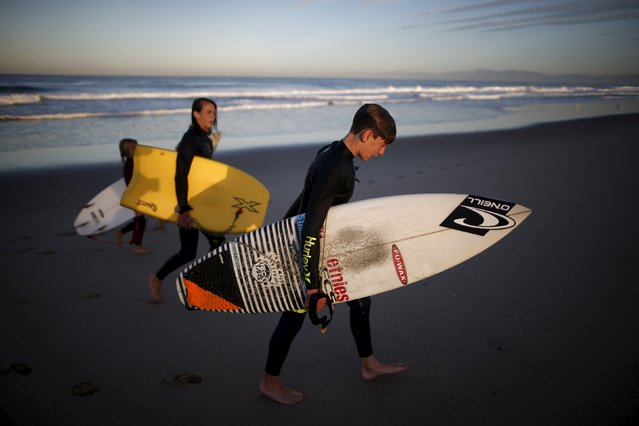Luke Personius, 12, (R) walks up the beach after surfing before school at sunrise in Hermosa Beach, California March 24, 2015. (Photo by Lucy Nicholson/Reuters)
