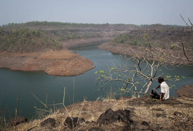 A villager sits on a hill overlooking part of Bhatsa dam on the outskirts of Denganmal village, Maharashtra, April 20, 2015. (Photo by Danish Siddiqui/Reuters)