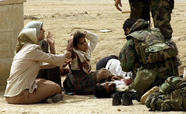 Iraqi civilians caught in crossfire are attended by a medic from the U.S. Marine Expeditionary Unit Fox Company as they push into southern Iraq to take control of the main port of Umm Qasr, March 2003. (Photo by Desmond Boylan/Reuters)