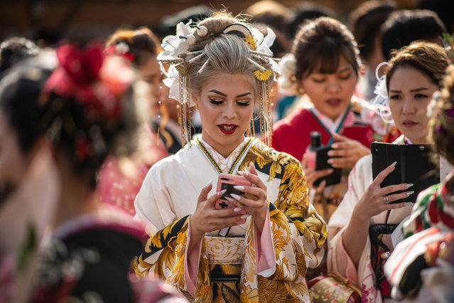 An Okinawan woman in a kimono checks her phone before attending a ceremony on Coming of Age Day on January 13, 2019 in Okinawa City, Japan. Coming of Age Day is a Japanese holiday held every January to celebrate people who have reached 20 – the official age of adulthood in Japan. Despite being a solemn affair in some parts of Japan, Okinawans have become known for their flamboyant and occasionally boisterous celebrations. (Photo by Carl Court/Getty Images)