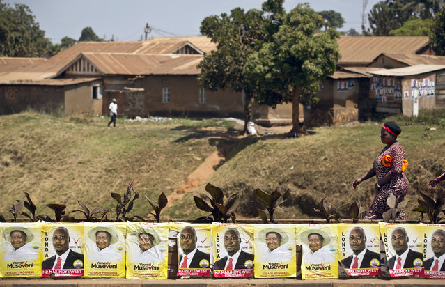 Pedestrians walk past campaign posters for long-time President Yoweri Museveni, as well as for local members of Parliament, on a street in Kampala, Uganda Wednesday, February 17, 2016. (Photo by Ben Curtis/AP Photo)