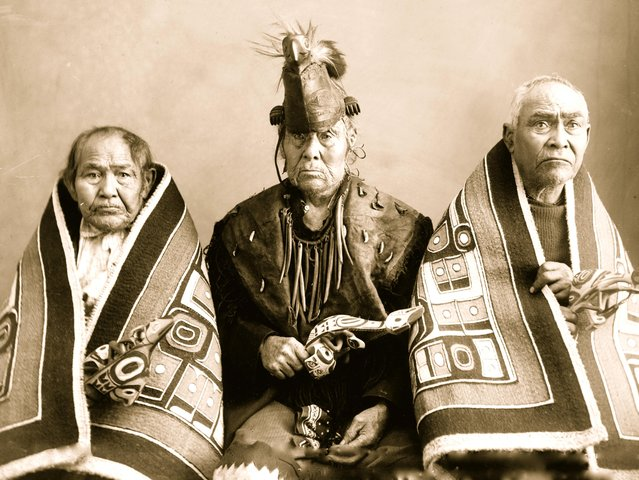 Three elderly Indians posed, half-length, seated, two wrapped in blankets, one wearing bird headdress and bone necklace, 1907. (Photo by Case & Draper/Buyenlarge/Getty Images)