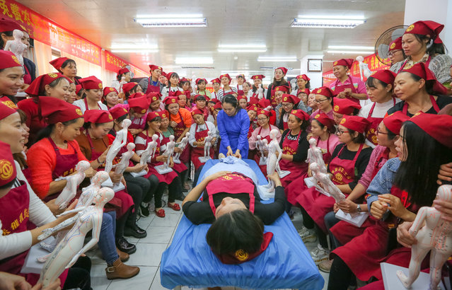 A teacher shows actions to students during a traditional Chinese medicine (TCM) galactagogue skills training at a staff's training center on January 7, 2019 in Haikou, Hainan Province of China. A free training course to teach Chinese medicine galactagogue skills was held in Haikou on Monday to help workers improve their employability skills as part of poverty alleviation work. (Photo by Yuan Chen/VCG via Getty Images)