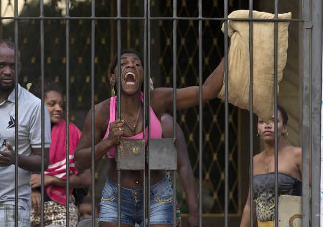 A woman protests to police before she and others are evicted from a building they invaded about a week ago in the Flamengo neighborhood of Rio de Janeiro, Brazil, Tuesday, April 14, 2015. (Photo by Silvia Izquierdo/AP Photo)