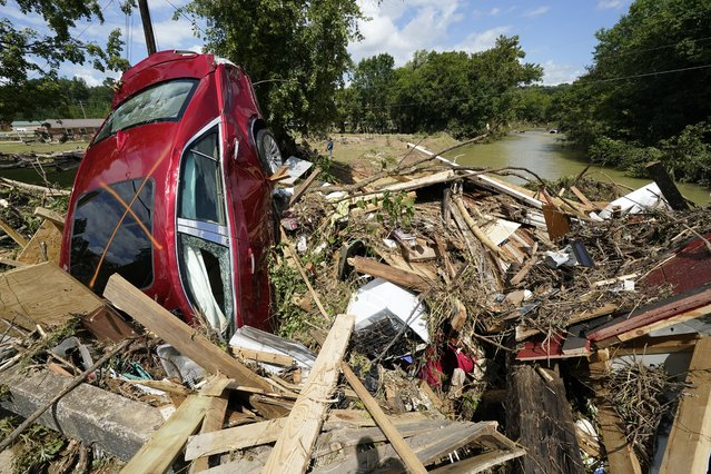 A car is among debris that washed up against a bridge over a stream Sunday, August 22, 2021, in Waverly, Tenn. Heavy rains caused flooding Saturday in Middle Tennessee and have resulted in multiple deaths as homes and rural roads were washed away. (Photo by Mark Humphrey/AP Photo)