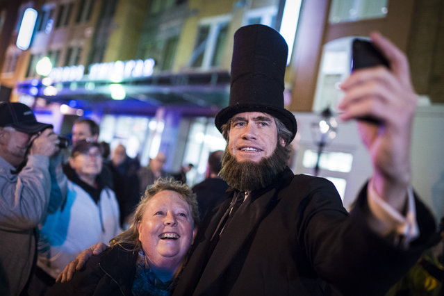 Scott Stewart dressed as Abraham Lincoln takes selfies with Susan Squires before a candlelight vigil where living historians recreated the scene from the night of April 14, 1865 on Tenth Street NW to commemorate the 150th anniversary of President Lincoln's assassination outside Ford's Theatre in Washington, DC on Tuesday April 14, 2015. (Photo by Jabin Botsford/The Washington Post)
