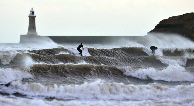 Two surfers brave the spring tide at Tynemouth as Britain is braced for further bad weather, on January 3, 2014. Britain is braced for the worst as a combination of high tides, heavy rains and strong winds are expected to bring yet more severe flooding to parts of the country. (Photo by Owen Humphreys/PA Wire)