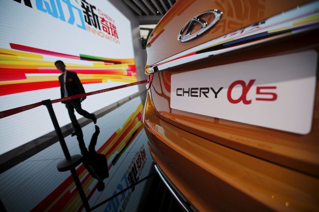 A visitor walks next to a Chery car during the 16th Shanghai International Automobile Industry Exhibition in Shanghai, April 20, 2015. (Photo by Carlos Barria/Reuters)