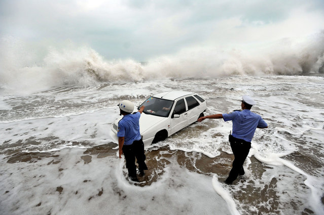 This picture taken on August 28, 2012, shows police trying to help remove a car surrounded by water after its owner parked it on the bank to watch waves brought on by Typhoon Bolaven in Qingdao, in northeast China's Shandong province. (Photo by AFP Photo)